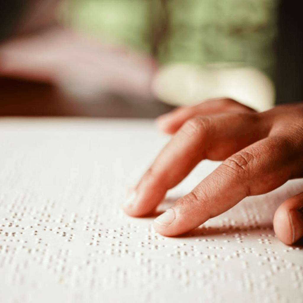 Accesibilidad en las comunicaciones - Persona leyendo un texto en braille